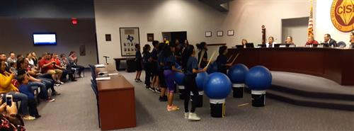 Drumfit team performs for the school board.